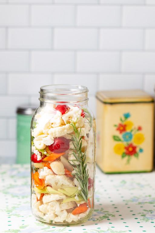 Jar of vegetables - cauliflower, celery peppers and rosemary.