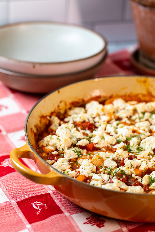 Yellow enameled pan filled with bubbling casserole topped with feta cheese.