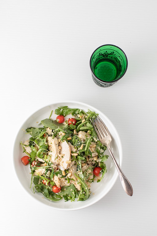 Big bowl of tabouli salad with a green glass of water.