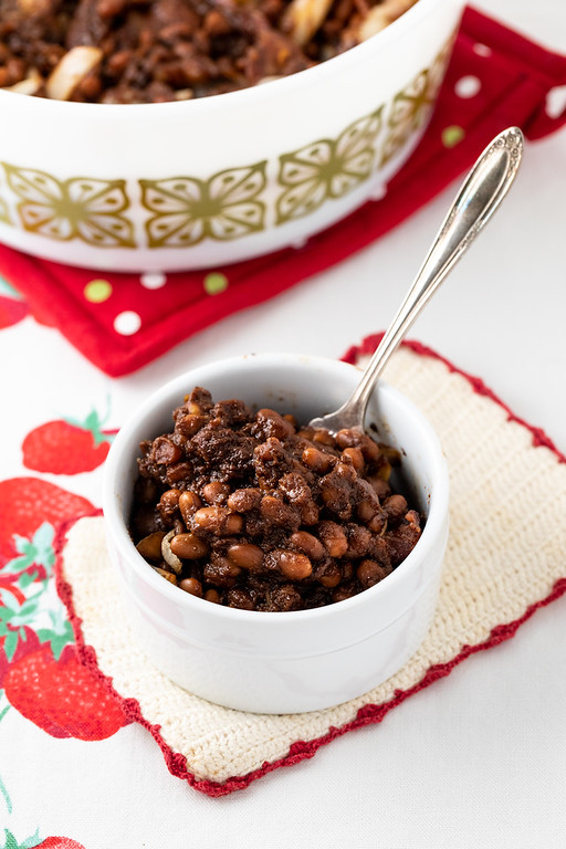Bowl of Boston Baked Beans with the casserole behind them.