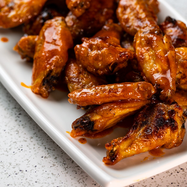 Close up of buffalo wings on a platter.