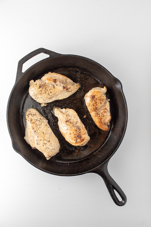 Cast iron skillet with 4 browned chicken breasts.