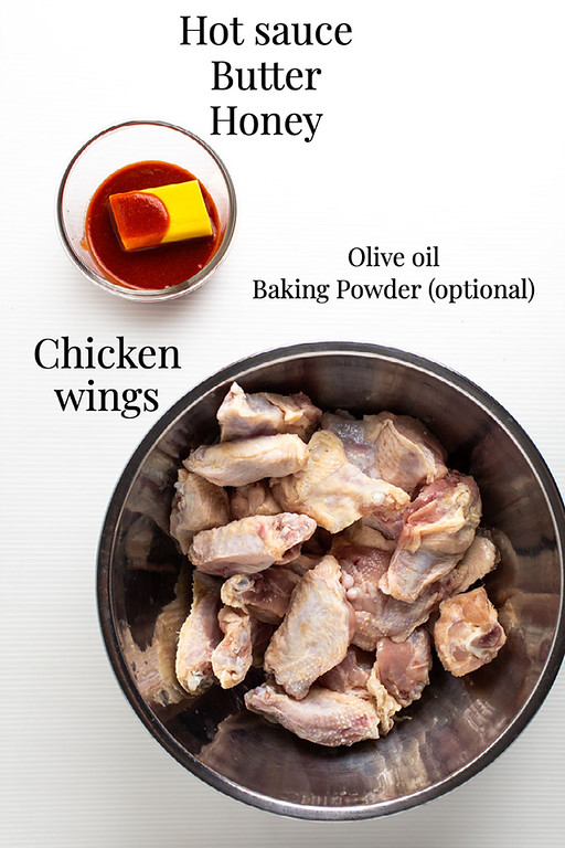 Hot sauce and butter in a small bowl, chicken wings in a metal bowl and text overlay.