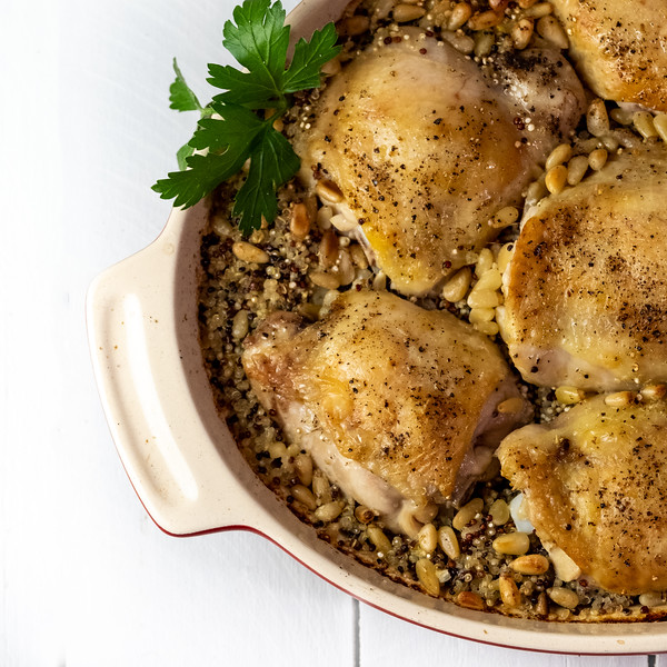 Close up of baked chicken thighs on a bed of quinoa.