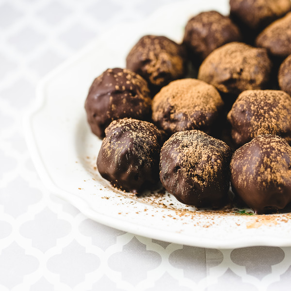 Plate of dark chocolate truffles dusted with coco powder.