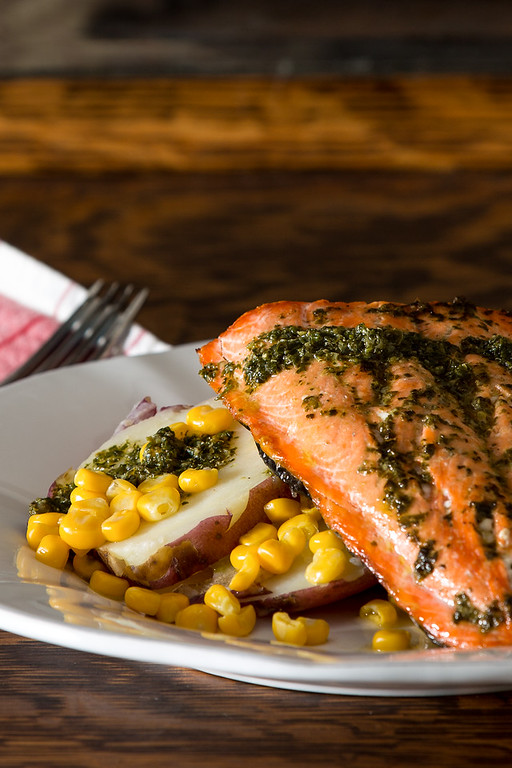 Salmon on top of corn and potatoes topped with basil vinaigrette.