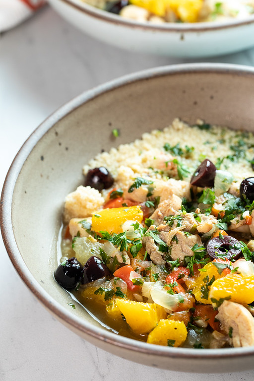 A bowl of citrus tagine with chicken, olives, and oranges.