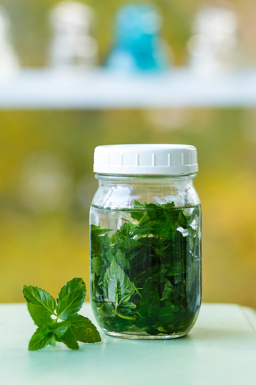 Mason jar filled with mint leaves and a clear liquid.