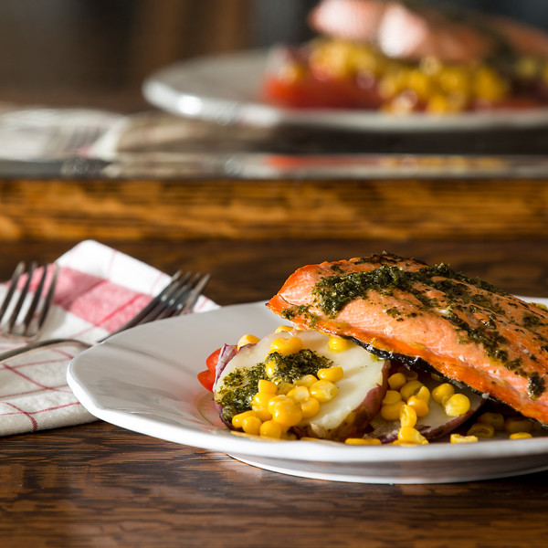 Salmon on a plate of corn and potatoes with a basil vinaigrette.