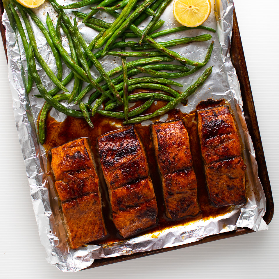 Glazed salmon on foil lined baking sheet with green beans.