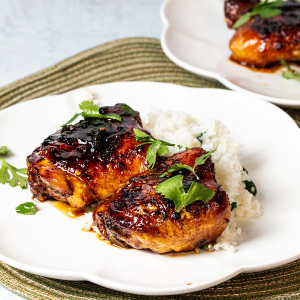 Two sticky Thai chicken thighs on a plate with rice.
