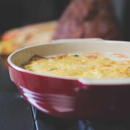 Red dish filled with Scalloped Potatoes with Gruyere