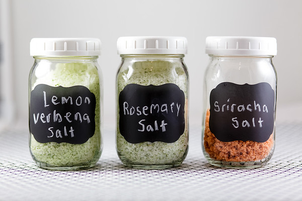 Three jars of salt with chalk labels reading: lemon verbena salt, rosemary salt, and sriracha salt