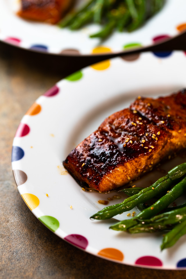 Salmon with a dark shiny crust and green beans on a colorful plate.