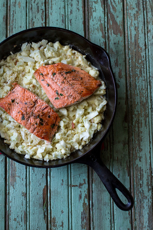 Salmon and cauliflower in a cast iron skillet on a blue wooden background.
