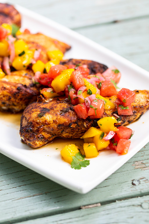Grilled chicken on a white plate, topped with a fruity salsa of watermelon and mango.