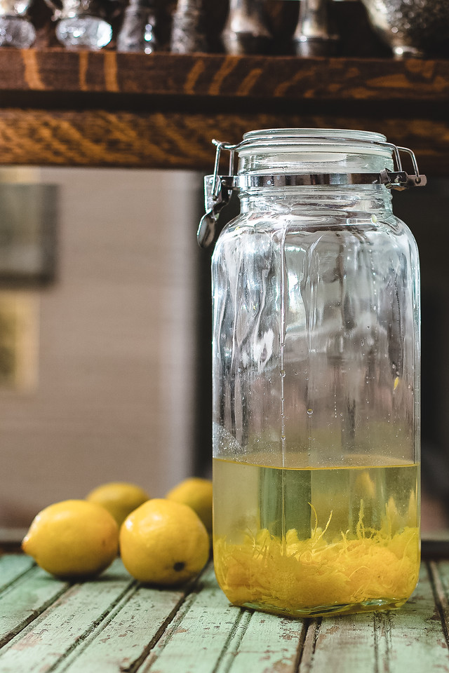 Jar with clear liquid and lemon zest in it