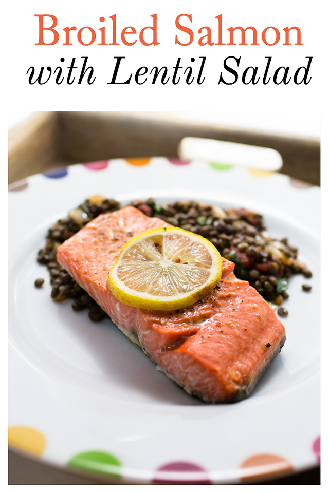 Salmon with lemon on top resting on a bed of lentils.