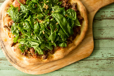 Harissa Lamb and Spinach pizza on a pizza peel