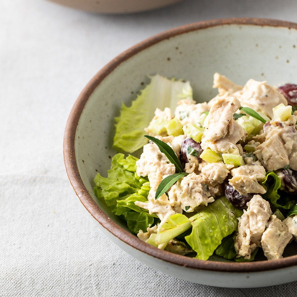 Bowl of chicken salad garnished with tarragon leaves.