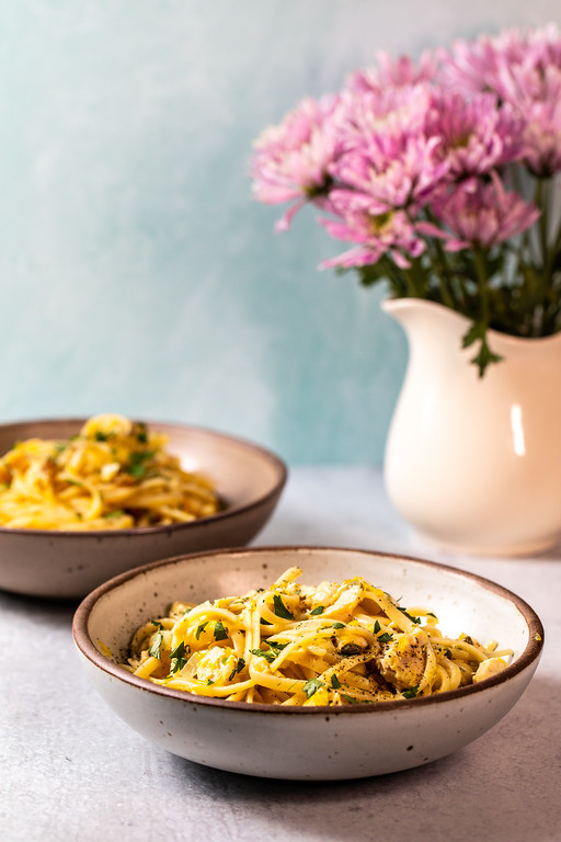 Two bowls of pasta with a vase of flowers behind them.