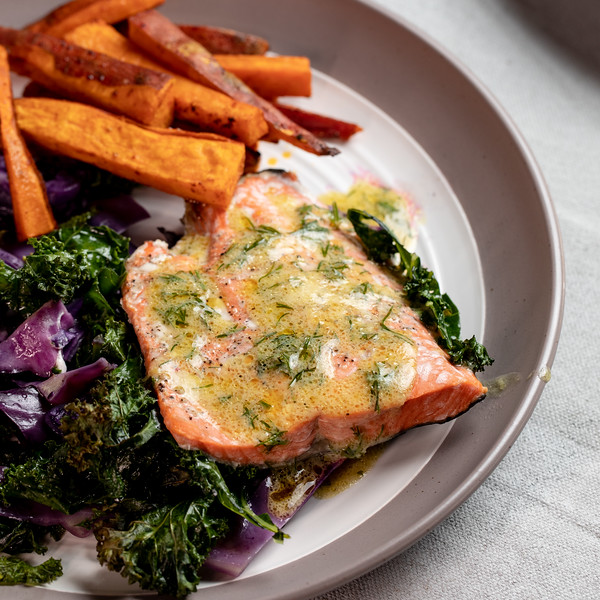 Plate with salmon, cabbage and kale drizzled with a vinaigrette.