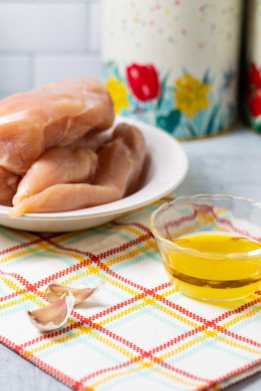 Boneless skinless chicken breasts in a bowl with a small bowl of lemon juice and olive oil and a couple of cloves of garlic.