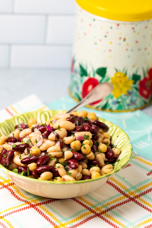 Bean salad in a bowl on top of checkered table cloth.