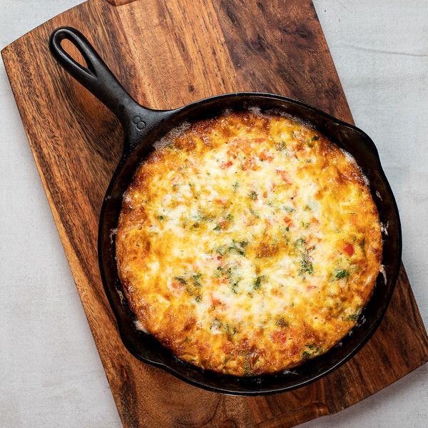 Cheesy baked frittata in a cast iron skillet.