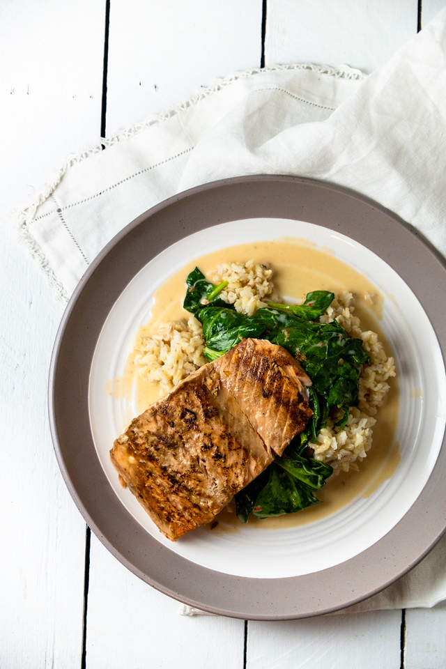 Overhead shot of salmon on top of spinach, on top of brown rice in a creamy orange sauce.