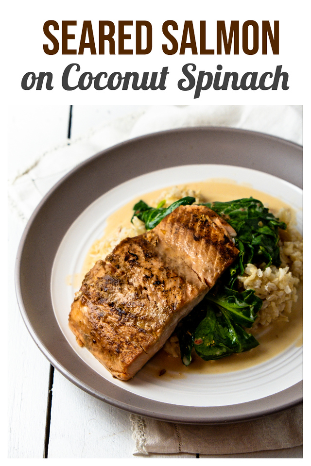 Brown and white plate with salmon on top of spinach on top of rice, with text that read seared salmon on coconut spinach
