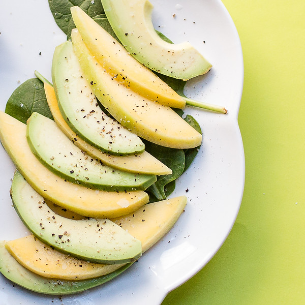 Avocado and mangoes sliced on a plate.