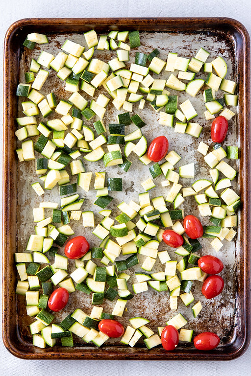 Baking sheet with cubed zucchini and squash and cherry tomatoes.