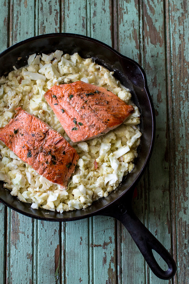 Cast iron skillet with cauliflower rice and salmon on top.