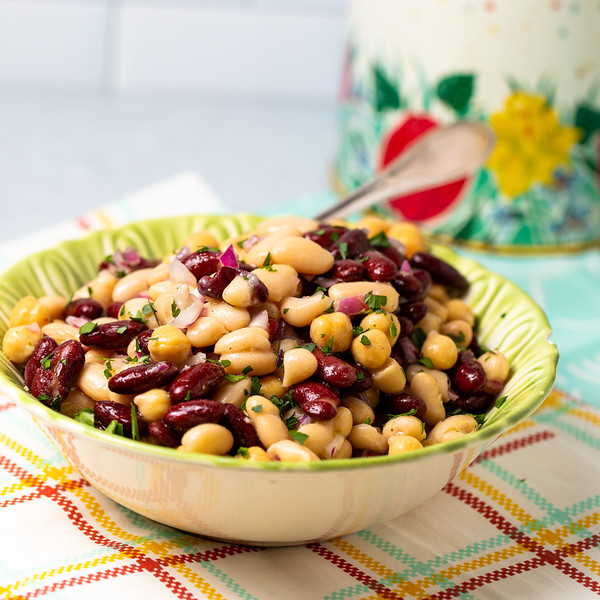 Green bowl filled with 3 bean salad on a colored tablecloth.