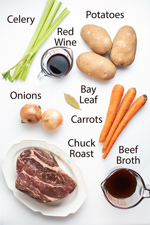 Celery, potatoes, red wine, bay leaf, onions, carrots, chuck roast and beef broth to make slow cooker pot roast.