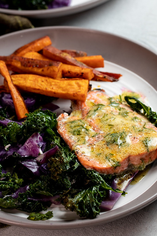 Salmon on a plate with cabbage, kale and sweet potato fries.
