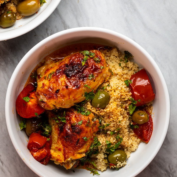 Bowl of couscous topped with harissa baked chicken thighs.