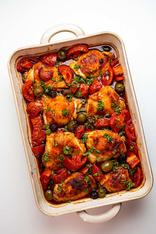 Baked chicken with olives and tomatoes in a large baking dish.