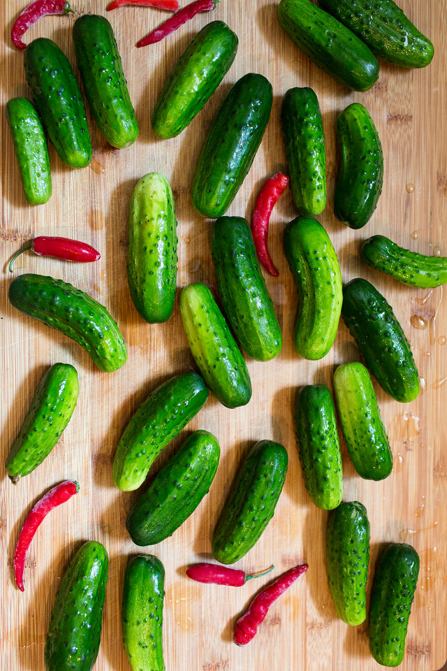 Small cucumbers and red peppers on a cutting board