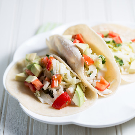 Plate with 3 fish tacos, garnished with cabbage, tomatoes and avocado.