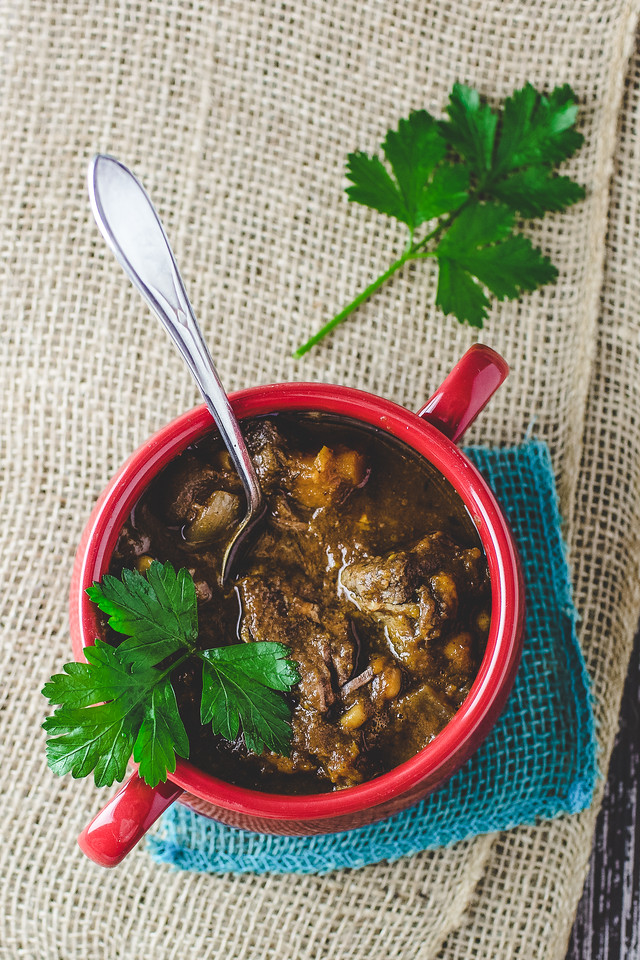 Red bowl filled with slow cooker beef stew garnished with parsley leaves on burlap background.