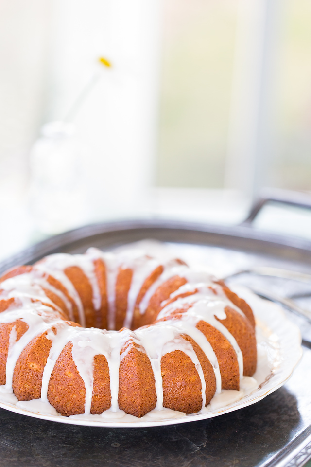 Glazed bundt cake on a silver tray.