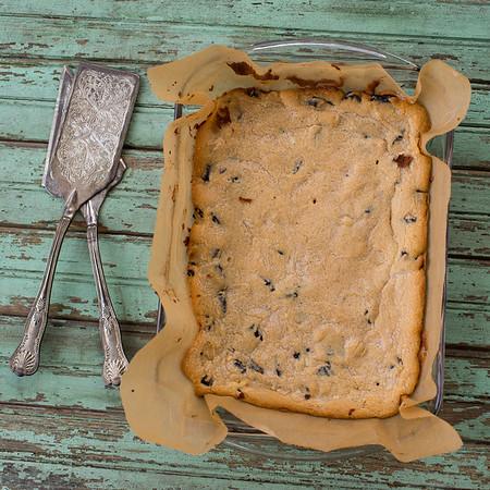 Overhead shot of cookies and cream blondies with vintage utensils.