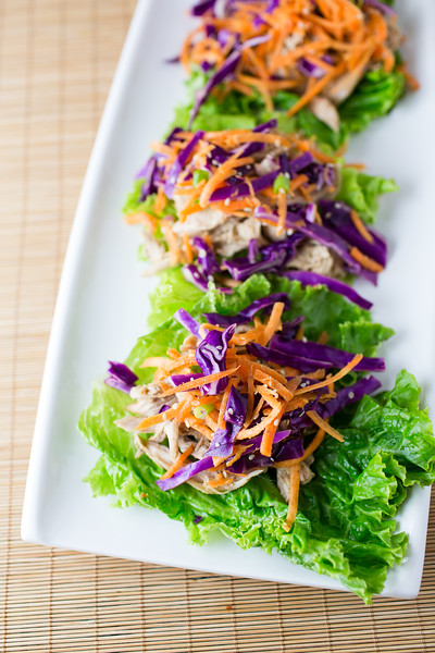 Plate of chicken lettuce wraps topped with a colorful carrot slaw.