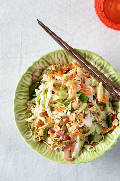 Bowl filled with Vietnamese Chicken Salad with chopsticks and an orange water glass.