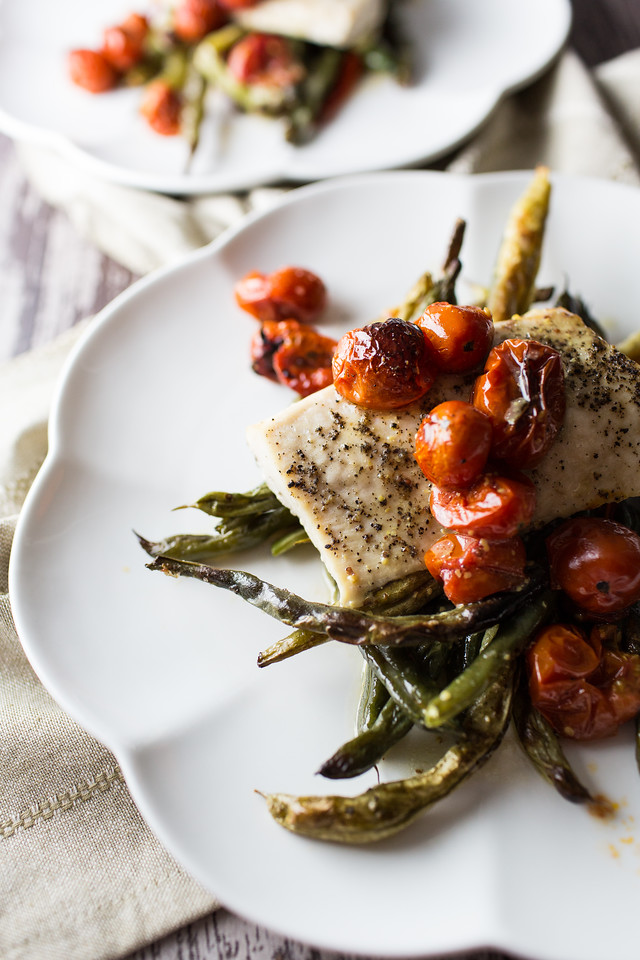 Scalloped plate with fish, green beans and tomatoes.