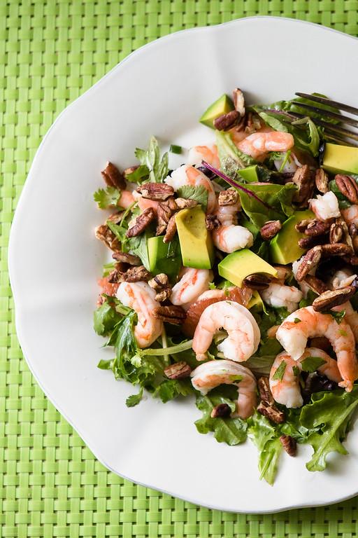 White plate with shrimp, avocado and grapefruit salad.
