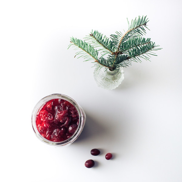 Overhead shot of brandied cranberries in a jar with cranberries beside it and a Christmas tree sprig.