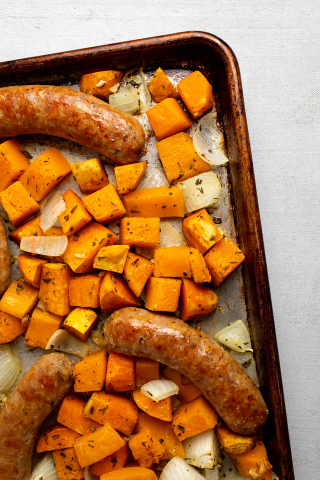 Sheet pan with sausages, sweet potatoes and onions.